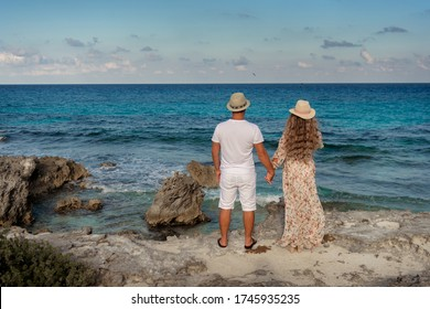A man and a woman walk on the seashore and look at the horizon.