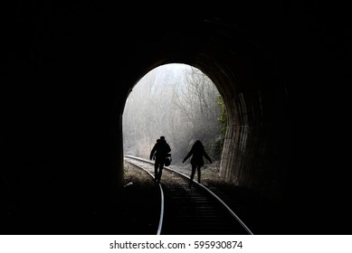 Man and woman walk the railway and get out from tunnel. Light on the end of the tunnel