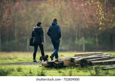 Man and woman walking dog in autumn park.
