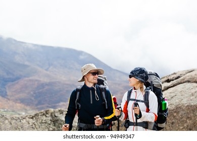 Man and woman walking in Himalaya mountains in Nepal, sport in nature. Young people traveling in Asia, trekkers on trail in wilderness.
