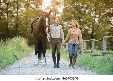 man and woman walking with horse on farmland