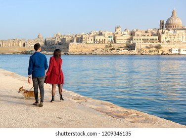 Man and woman walking near the sea with the view to Valletta, Marsamxett. Man and woman walking with doggy near the sea. Romantic couple near the sea with vie to Valletta, Malta