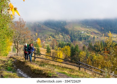Man and Woman Walking on Rural Trail among colorful Autumnal Forest with Backpacks Warm Sunny Day