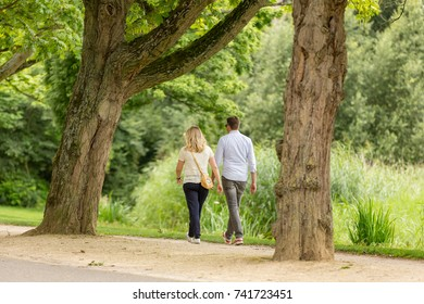 A man and woman walking through the Amsterdam Vondelpark in the Netherlands.