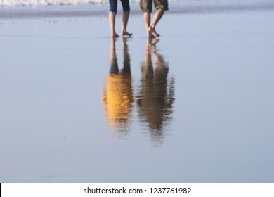 A man and woman walking a wet sandy beach, barefoot; Their feet are blurred out and their reflection is clear.