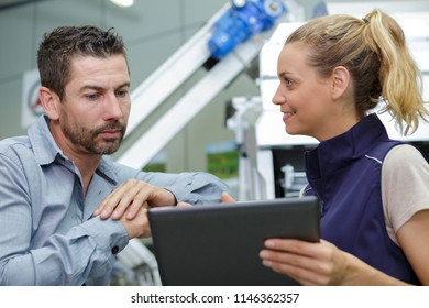man and woman in warehouse discussing over tablet