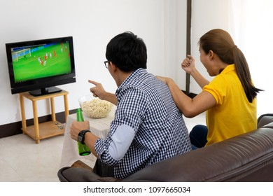 man and woman watch Football match on tv broadcast program cheer and existing together in family