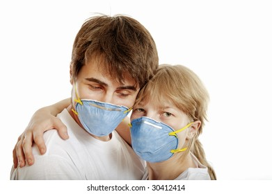 Man and woman wearing  respirators hug one another against white background