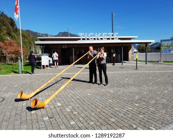 The man and woman wind musical alphorn in front of ticket counter, Pilates mountain , Switzerland.on 12 October 2018.