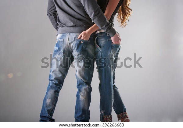 a man and a woman without the upper part of the body in blue jeans on a grey background