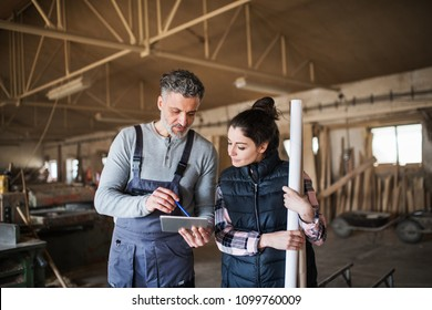 Man and woman workers with tablet in the carpentry workshop.