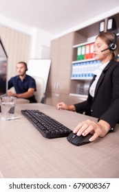 Man and woman working at customer service help line. Wearing headphones