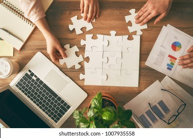 Man and woman working in the office. Collaborative teamwork. People are trying to connect couple puzzle piece. Symbol of association and connection. Concept of business strategy.