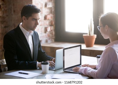 Man and woman working on computers. Serious male and female looking at each other struggling for leadership. Concept of sexism, workplace inequality, discrimination based on person sex or gender