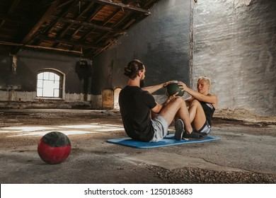 Man and woman working out with medicine ball in an old building
