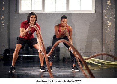 Man and woman working out with ropes in gym