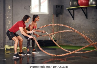 Man and woman working out with ropes in the gym