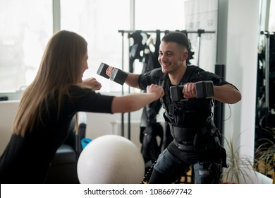 Man and woman working out together EMS training. Personal trainer helps the girl during the exercise