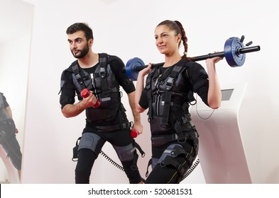 Man and woman working out together EMS training closeup, power pose