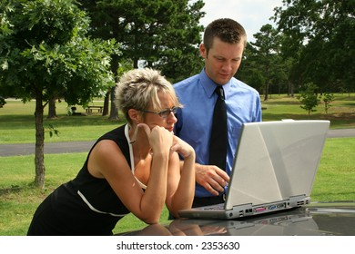 Man and woman working outdoors on computer.