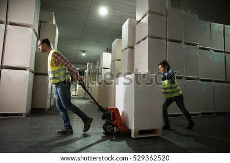 Man and a woman working with small forklift in a warehouse. First in first out, last in last out, just in time concept photo.