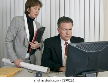 A man and a woman in a workplace setting appearing to be working together.