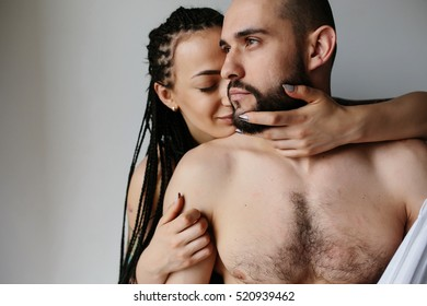 man and woman wrapped in a blanket at the bedroom