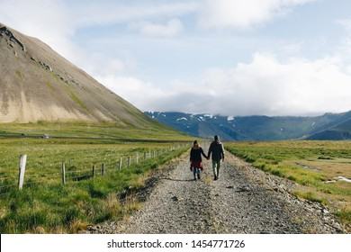 Man and woman, young or adult couple in outdoor outfit or gear walk in national park or mountain landscape, hold hands and enjoy slow life, contemplate emerged in nature and fresh air