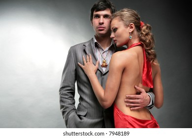 Man and woman. Young woman embraces man. Woman in a red dress. Woman looks at the man.
