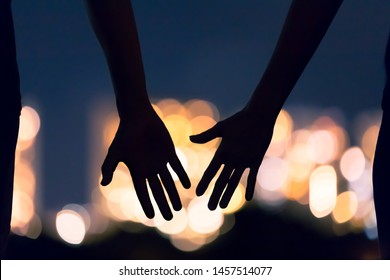 Man and woman's hands coming together facing the city night lights. People, love and relationships concept.