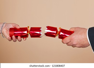 A man and womans hands pulling a red Christmas cracker.