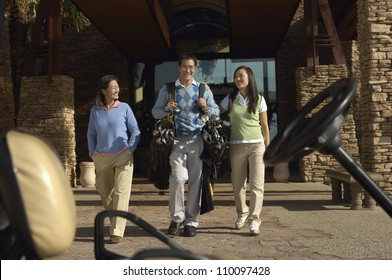 Man with women carrying golf bags walking toward golf cart
