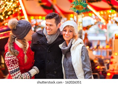 Man and women or friends during advent season or holiday in front of a carousel or merry-go-round on the Christmas or Xmas market
