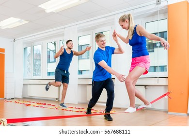 Man and women getting guidance at tightrope walking at health club gym
