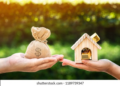 Man and women hand hold a home and gold bar and a money bag put together on sunlight in the public park, Saving money for buy a new house or loan for plan business investment of real estate concept.
