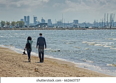 A man and a women having a quiet walk on the Pirita beach in Tallinn, Estonia. You can see the skyline of the city in the background.