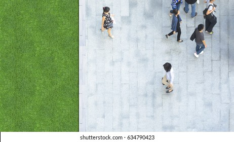 man and women people walk on across the pedestrian concrete and grass landscape in the city street (Aerial top view)