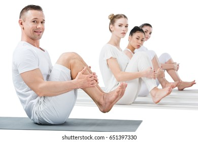 man and women performing boat position on yoga mats isolated on white