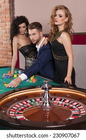Man and women playing roulette at casino
