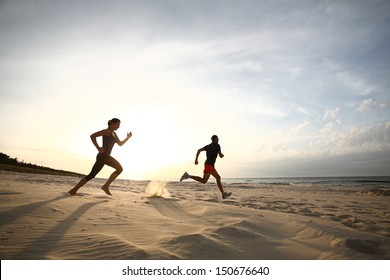 Man and women running on beach at sunset