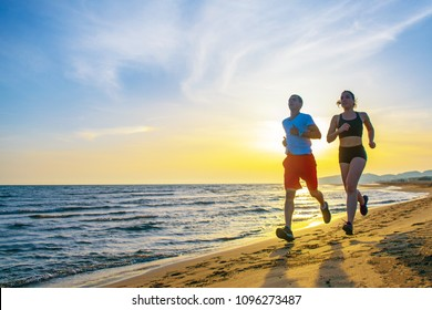 Man and women running on tropical beach at sunset