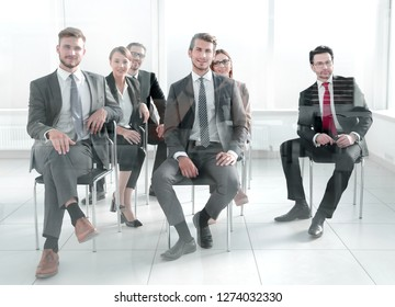 Man and women sitting on chairs in row