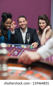 Man and women sitting at roulette table smiling in casino