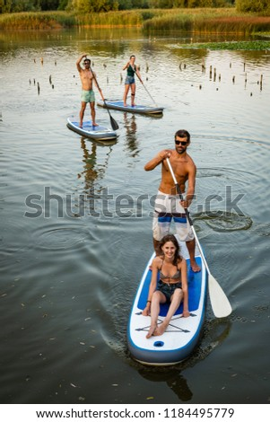 Man and women stand up paddleboarding on lake. Watersport on lake. Male and females tourists during summer vacation.