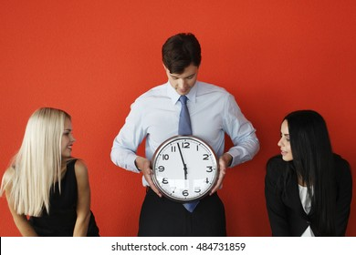 Man and women with wall clock on red background, deadline concept
