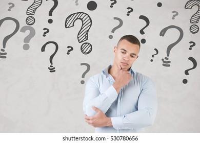 Man wondering with question marks around him