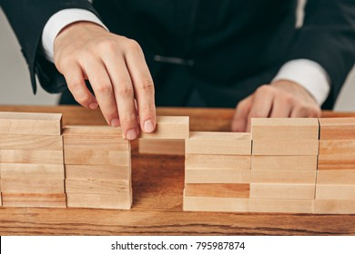 Man and wooden cubes on table. Management concept