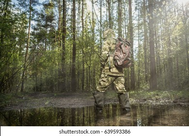 Man in the woods dressed in camouflage with backpack. Standing in a puddle. Sun flare on the right side.