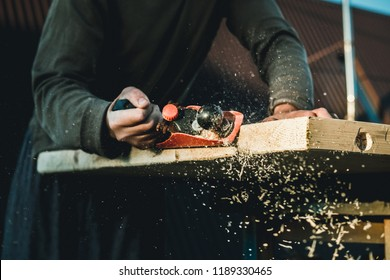 Man woodworker carpenter working with a hand plane. Planing a board is flying shavings. Master manual labor.
