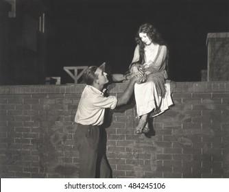 Man wooing woman sitting on brick wall